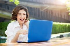 笑和指向在膝上型计算机屏幕上的愉快的亚裔女孩胜过 免版税库存照片
