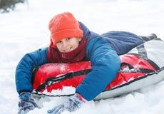 笑和显示兴奋的英俊的青少年,当他滑下坡时 雪管材在户外冬日 免版税库存图片