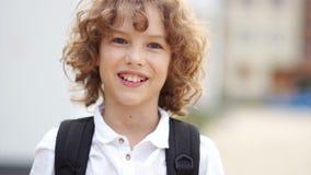 笑和看照相机的青春期前的卷曲蓝眼睛的男孩 男小学生在一件白色衬衣打扮并且运载a 影视素材