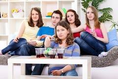 笑和看电视的青年人 免版税库存图片