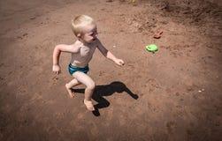 笑和跑在海滩的男孩 免版税库存图片