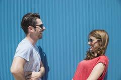 笑和采取交谈的朋友或夫妇反对b 免版税库存图片