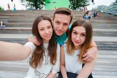 笑和采取在街道的小组愉快的青少年的朋友一selfie 观看三个的朋友拍照片与 免版税库存图片