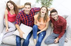 笑四个愉快的朋友,当坐长沙发时 库存图片