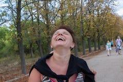 笑在公园的妇女 免版税库存照片