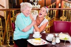 笑在咖啡馆的老婆婆和孙女 库存照片
