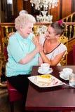 笑在咖啡馆的老婆婆和孙女 库存图片