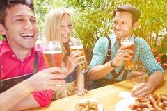 笑在啤酒庭院里的朋友 免版税库存照片