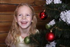 笑在圣诞树附近的美丽的愉快的小女孩 免版税库存照片