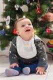 笑在地板上的一个10个月大婴孩由圣诞树 库存图片