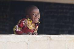 笑在墙壁后的英俊的非洲男婴在学校 免版税库存照片