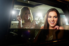 笑在大型高级轿车背后的两名迷人的妇女 库存图片