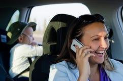 笑在她的移动电话的妇女驱动器 库存照片