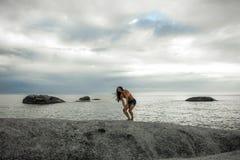 笑在岩石的妇女在Bakovern海滩,开普敦的日落 免版税库存图片