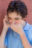 笑在手机的男孩 图库摄影