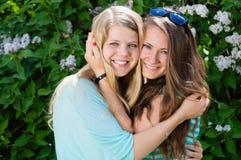 笑在春天或夏天的两个青少年的女朋友户外 免版税库存照片