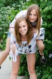笑在春天或夏天的两个青少年的女朋友户外 免版税库存图片