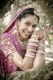 笑在树下的年轻美丽的印地安印度新娘用被举的被绘的手 免版税库存图片