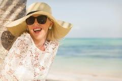 笑在棕榈树下的快乐的妇女在海滩 免版税库存照片