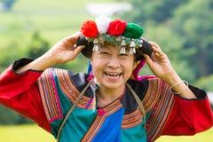 笑在水稻领域五颜六色的服装礼服的愉快的小山部落 免版税库存照片