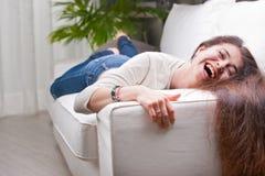 笑在沙发的愉快的女孩 免版税库存图片