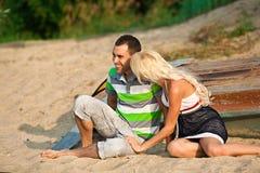 笑在海滩的男孩和女孩 免版税库存图片