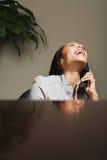 笑在电话的女商人 库存图片