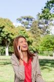 笑在电话的妇女,当查找往星期日时 免版税库存图片