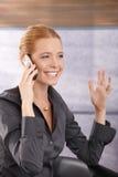 笑在电话的愉快的女实业家 免版税库存照片