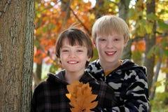笑在秋天森林里的两个男孩 免版税库存图片