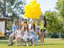 笑在草坪的小组美丽的女孩 免版税库存图片