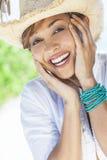 笑在草帽的美丽的混合的族种妇女 免版税库存图片