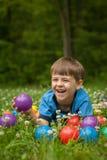 笑在草的小男孩 免版税库存照片