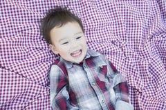 笑在野餐毯子的逗人喜爱的年轻混合的族种男孩 库存照片