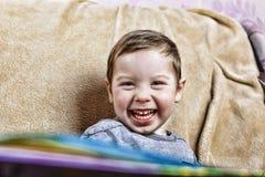 笑在长沙发的小愉快的男孩hile开会 关闭 库存图片