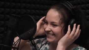 笑在音乐演播室的女孩 关闭有耳机的少女 声音录音 音乐录音 女孩在声音演播室是s 影视素材