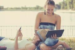 笑在移动设备的愉快的妇女朋友浏览社会媒介 免版税图库摄影