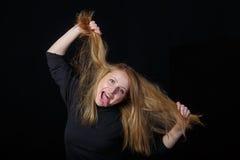 笑在黑背景的快乐的年轻白肤金发的妇女 免版税库存照片
