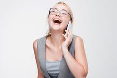 笑大声谈话在电话的年轻金发碧眼的女人 库存图片