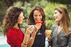 笑女性的朋友,当喝鸡尾酒时 库存图片