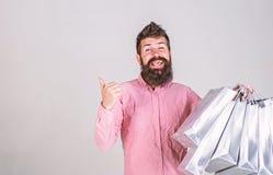 笑容的行家推荐买 有胡子和髭的人运载束购物带来,灰色背景 免版税图库摄影