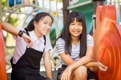 笑对于儿童操场的快乐的亚裔少年 库存图片
