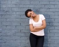笑对灰色墙壁的美丽的年轻黑人妇女 图库摄影