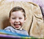 笑小愉快的男孩,当坐长沙发时 关闭 免版税库存照片