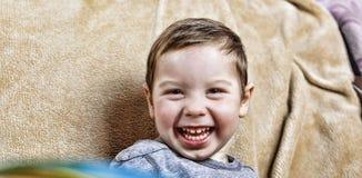 笑小愉快的男孩,当坐长沙发时 关闭 图库摄影