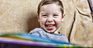 笑小愉快的男孩,当坐长沙发时 关闭 免版税图库摄影