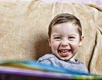 笑小愉快的男孩,当坐长沙发时 关闭 免版税库存图片