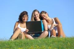 笑小组三个少年的女孩,当观看室外时的膝上型计算机 库存照片