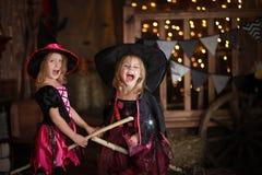 笑帚柄的两个小女孩巫婆 童年你好 免版税库存图片