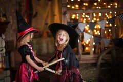 笑帚柄的两个小女孩巫婆 童年你好 免版税图库摄影